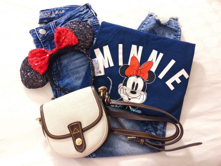 Disney Outfit flat lay of jeans, white crossbody purse, Minnie Mouse ears, and Minnie t-shirt.