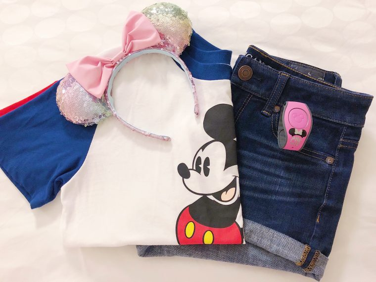 Flat Lay Photo of Mickey Mouse t-shirt, iridescent Minnie Mouse ears, and cuffed jean shorts.