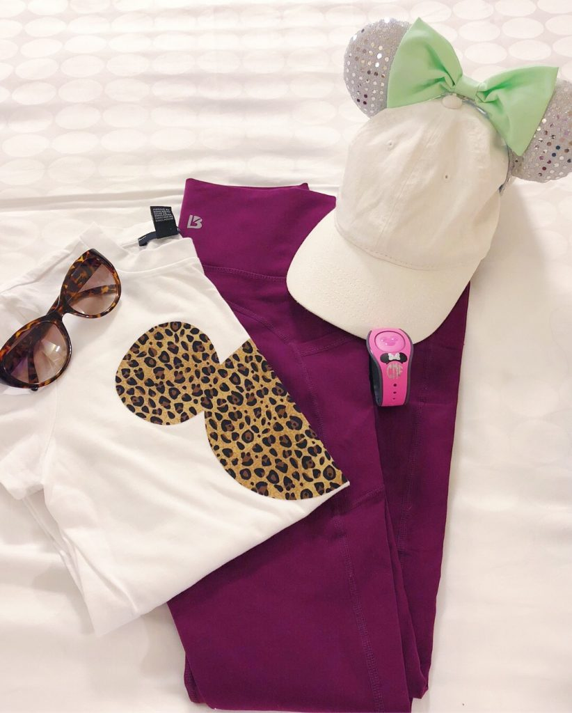 Flat Lay Photo of purple leggings, cheetah print mickey head t-shirt, white hat, silver Minnie ears.