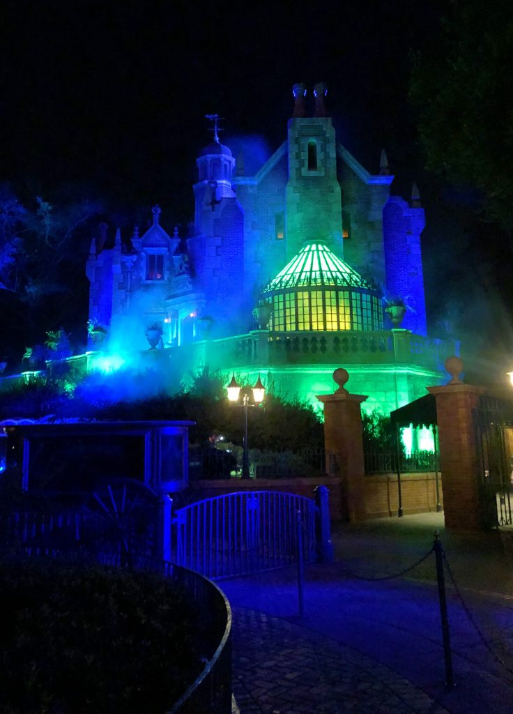Disney World Haunted Mansion lit up in blue and green for Halloween.